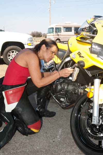 A female racer works on her bike at Hallett.