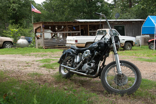 An old Harley Sportster sits in the grass near the Crooked Branch Saloon in Eastern Oklahoma.