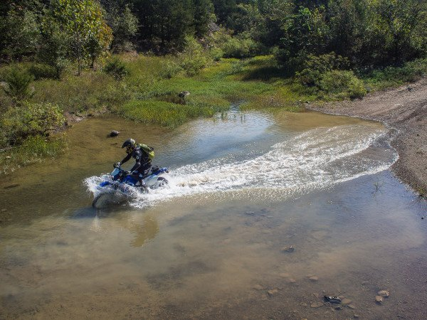 Dirk Mathews rides his Suzuki DRZ-400 through a nearby river north of Tuskahoma.